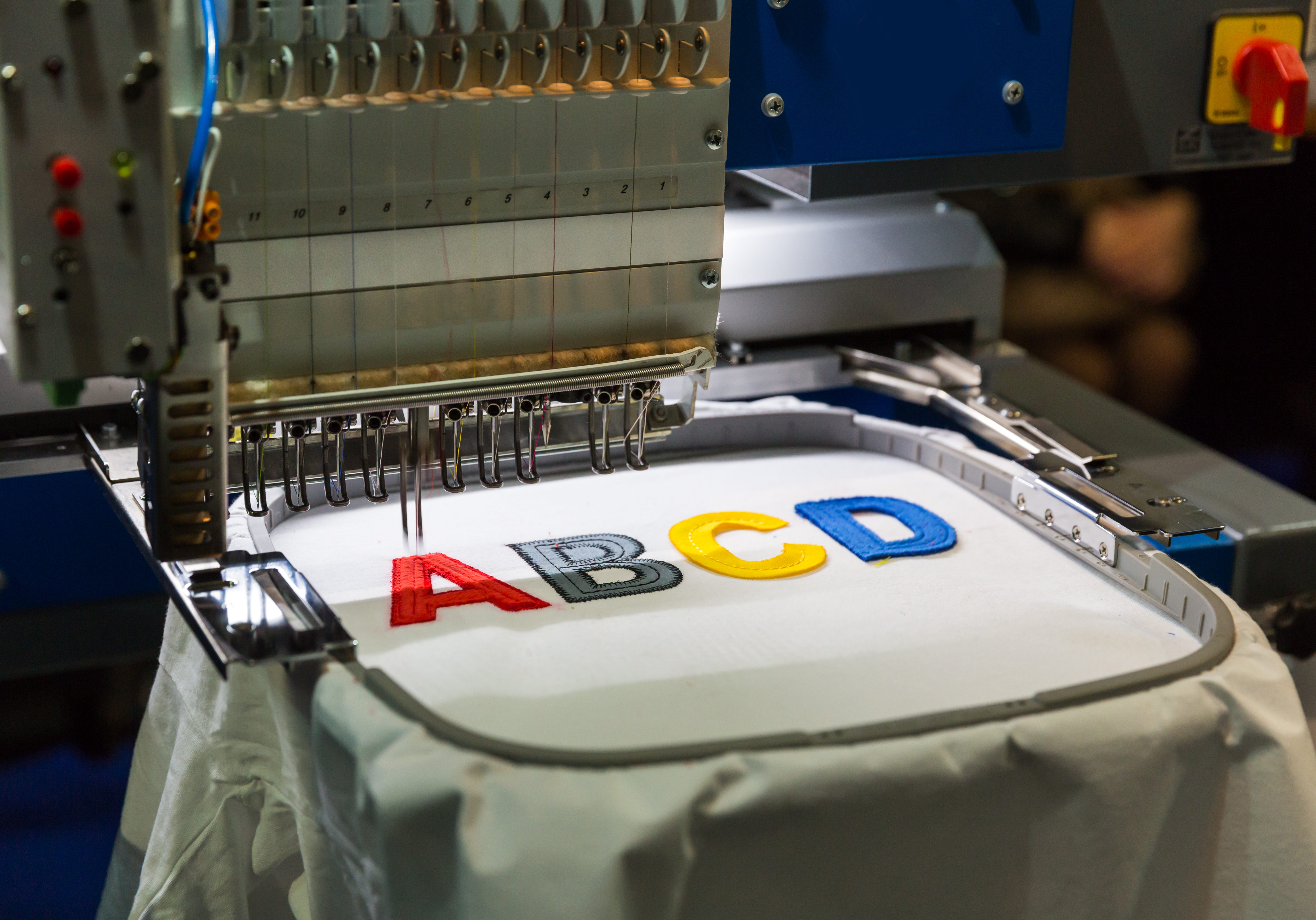 Professional sewing machine embroidery color letters. Textile fabric, nobody. Factory production, sew manufacturing, needlework technology